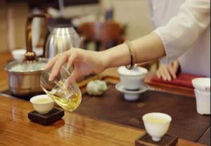 一隻手提起茶壺倒茶