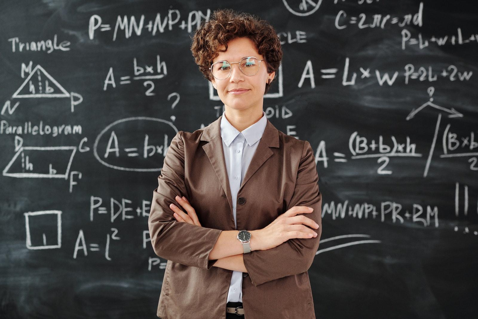 一名女教師站在充滿公式的黑板前