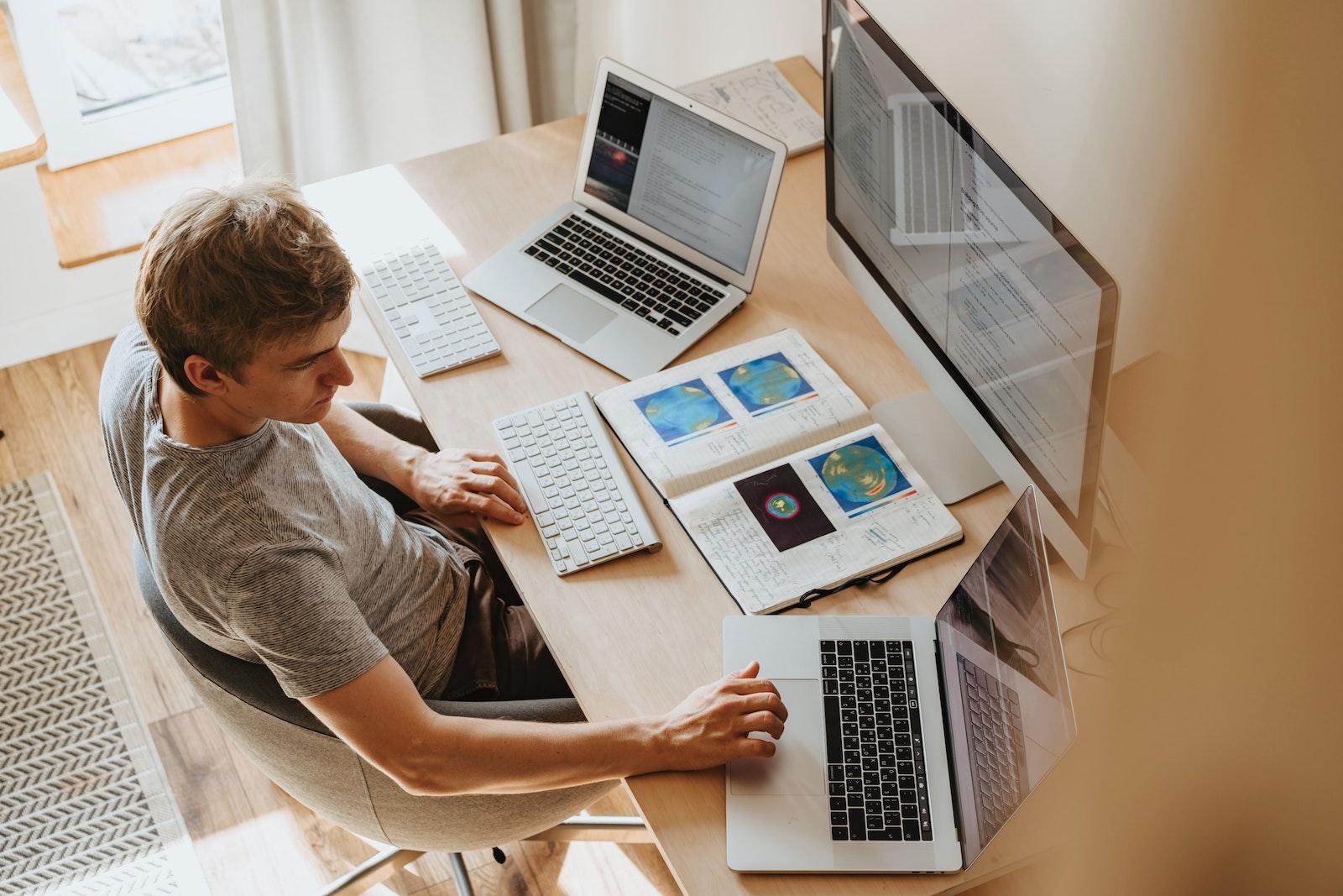一個男人正在使用三台電腦設備工作