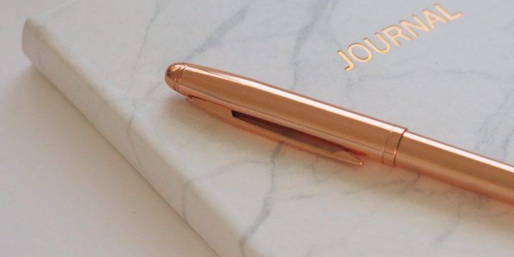 一本筆記本上有一支鋼筆